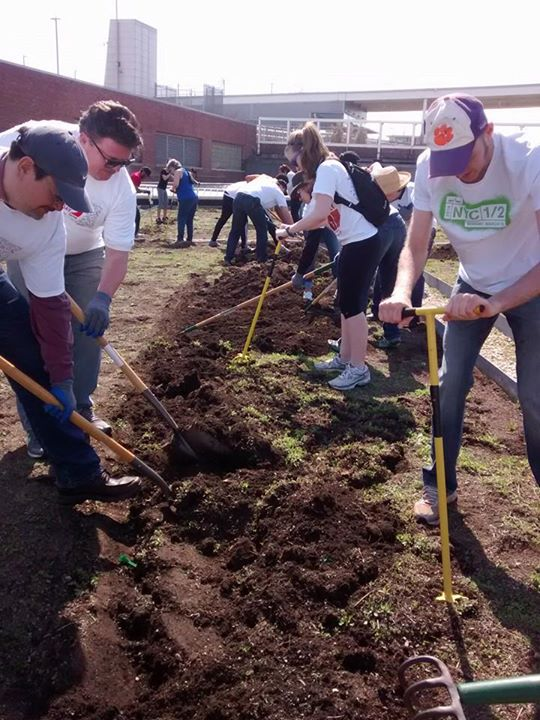 Rotary club members tilling the planting soil